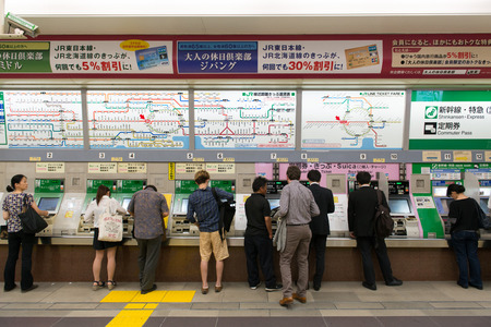 fare: Shinjuku, Tokyo, Japan - June 2, 2015: People buying railway tickets at the vending machines under JR line in Shinjuku station, Tokyo.  Ticket fare is shown in both English and Japanese above the vending machines.