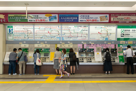 fare: Shinjuku, Tokyo, Japan - June 3, 2015: People buying railway tickets at the vending machines under JR line in Shinjuku station, Tokyo.  Ticket fare is shown in both English and Japanese above the vending machines. Editorial