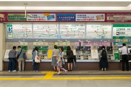 Shinjuku, Tokyo, Japan - 3 juni 2015: Mensen kopen van treinkaartjes bij de automaten onder JR lijn in Shinjuku station, Tokyo. Ticketprijs wordt getoond in zowel Engels en Japans boven de automaten.