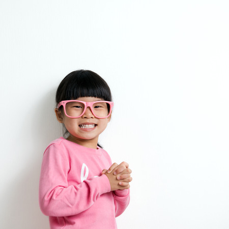 winter fashion: Portrait of happy Asian child wearing pink glasses