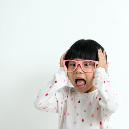 surprised child: Portrait of happy little Asian girl wearing pink glasses