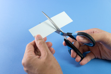 scissors: Hand cutting plain paper into two pieces with scissors Stock Photo