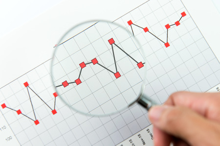 Close up of analysing report graph with magnifying glass