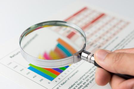 돋보기와 재무 데이터를 분석하는