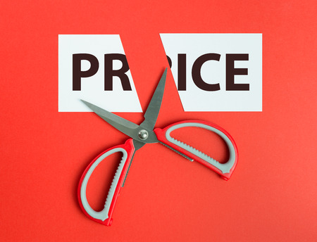 price cutting: Scissors cutting paper with the word price written on it Stock Photo