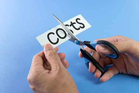 reduce: Scissors cutting paper with the word costs on it