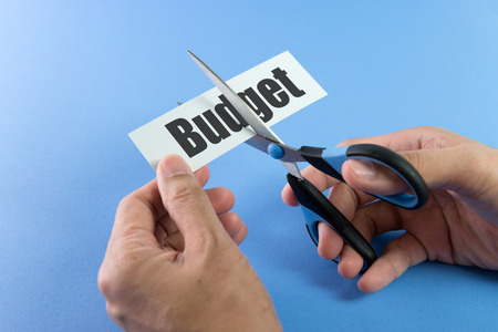cutting costs: Scissors cutting paper with the word budget on it