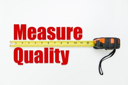 Cinta métrica sobre la medida de las palabras y la calidad en el fondo blanco Foto de archivo