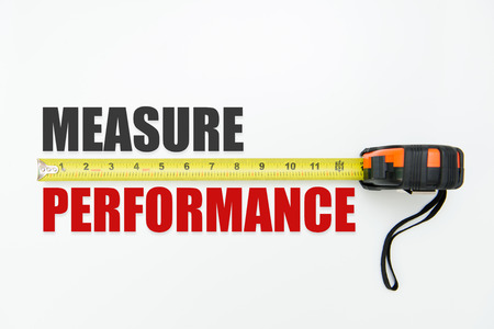 Measuring tape over the words measure and performance on white background Stock Photo