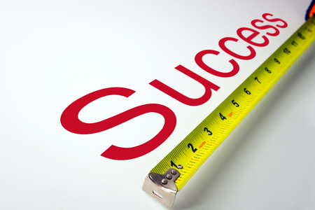 Measuring tape over the word success on white background