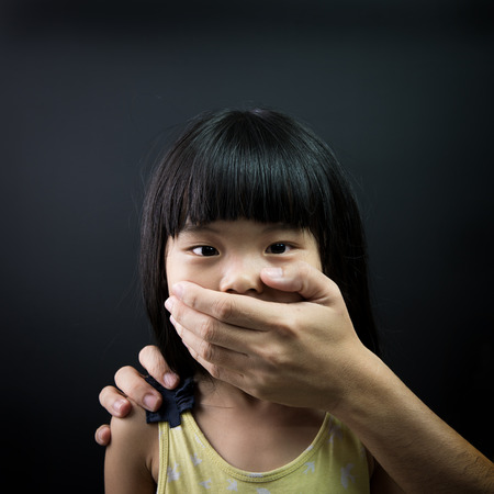 Niño asiático que es secuestrada, con la boca cubierta por una mano adulta