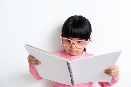 eyewear: Portrait of Asian child reading book on white background