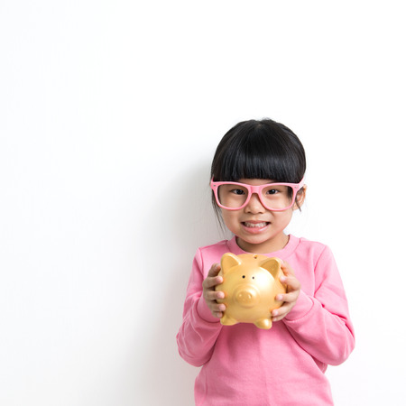 money saving: Child savings, investment or money concept illustrated with Asian kid holding a piggy bank