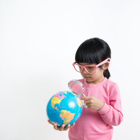 toddler: Little Asian girl looking at the earth globe with magnifying glass