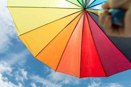 rainbow umbrella: Hand holding rainbow umbrella against cloudy blue sky Stock Photo
