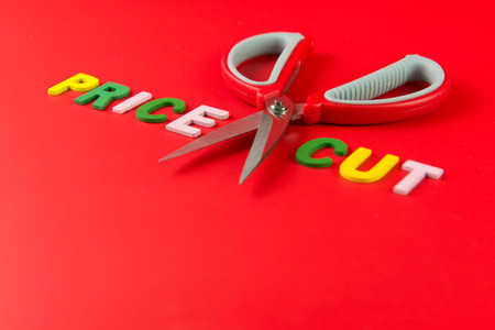 price cutting: Price cut concept with pair of scissors between the word price and cut on red background
