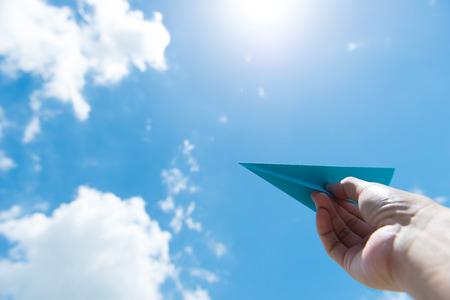 Mano de lanzar avión de papel hacia el cielo azul nublado
