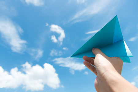 Hand launching paper plane toward cloudy blue sky