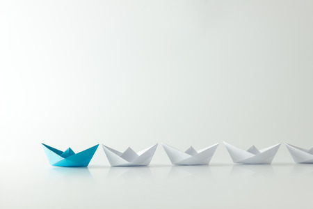 leadership: Leadership concept with blue paper ship leading among white Stock Photo