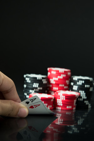 aces: Hand with pocket aces and stacks of poker chips