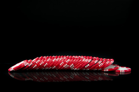 Red poker chips in a row over black background Stock Photo