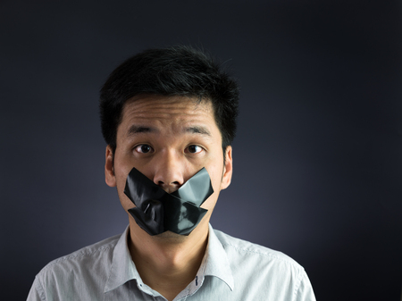 no fear: Man with black tape over his mouth on black background