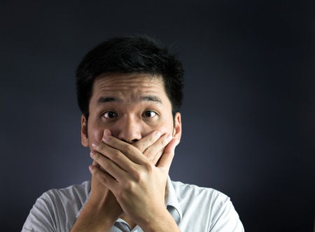 mouthed: Silenced concept, with man covered his mouth with his hand