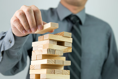 ジェンガ タワーに木製のブロックを配置する実業家のクローズ アップ