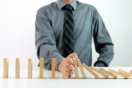 problem solution: Businessman stops domino effect for business solution and successful intervention