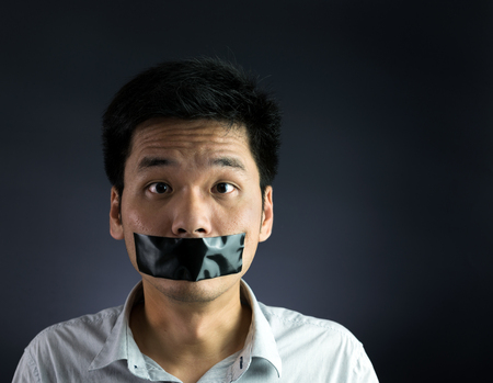 Man with black tape over his mouth on black background