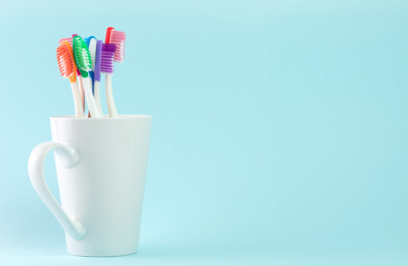 oral care: Multicolor toothbrushes in white mug, with copyspace