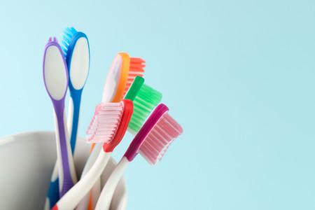 白いマグカップ多色歯ブラシのクローズ アップ