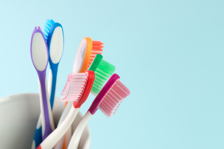 Close up of multicolor toothbrushes in white mug