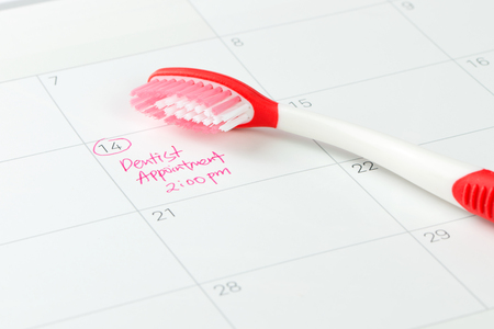 Red toothbrush on dentist appointment reminder on a calendar