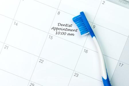 Cepillo de dientes azul en recordatorio de la cita del dentista en un calendario Foto de archivo