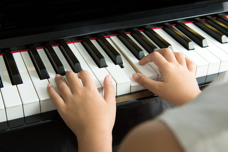 children learning: Close up of little girl playing music on piano Stock Photo