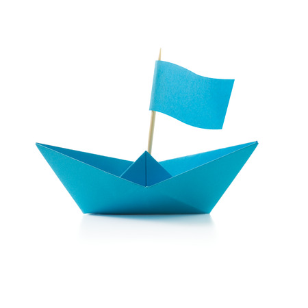 Origami blue paper boat with flag on white background