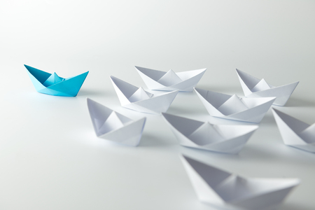 journeys: Leadership concept with blue paper ship leading among white Stock Photo