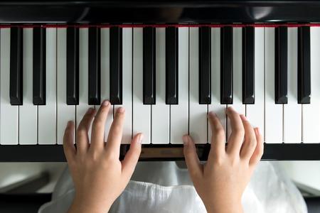 ピアノで音楽を再生少女のクローズ アップ 写真素材