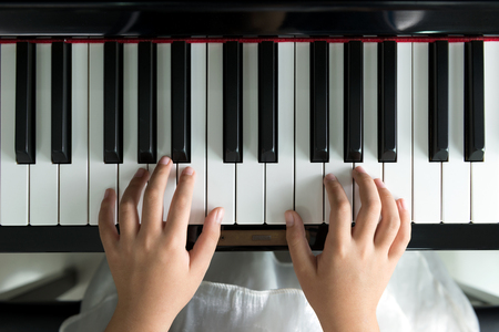 Close up of little girl playing music on piano Foto de archivo