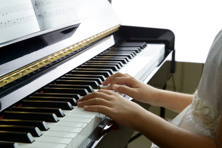 Close up of little girl playing music on piano 스톡 콘텐츠
