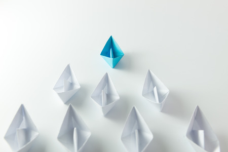 competition success: Leadership concept with blue paper ship leading among white Stock Photo