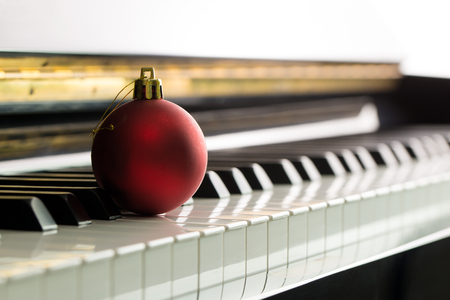 Christmas music illustrated with red Christmas ball on piano keyboard