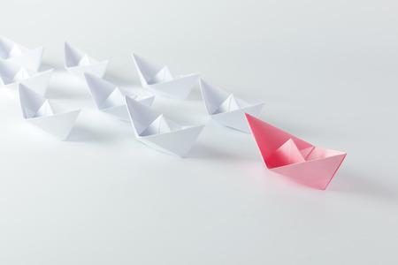 liderazgo: concepto de la direcci�n de la mujer con el barco de papel de color rosa que lleva entre los blancos Foto de archivo