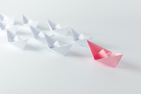 industry concept: Woman leadership concept with pink paper ship leading among white