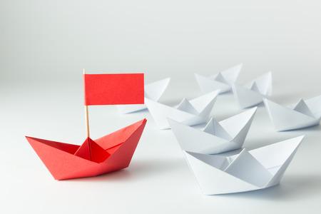 Concepto de la dirección con la nave de papel rojo líder entre blanco