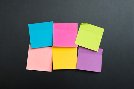 multi colors: Blank multi colors sticky notes arranged in two rows on black board Stock Photo