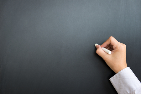 pizarron: Businessman hand with chalk on empty black board