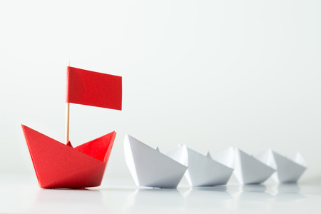 boat: Leadership concept with red paper ship leading among white Stock Photo