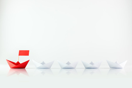 Leadership concept with red paper ship leading among white Foto de archivo